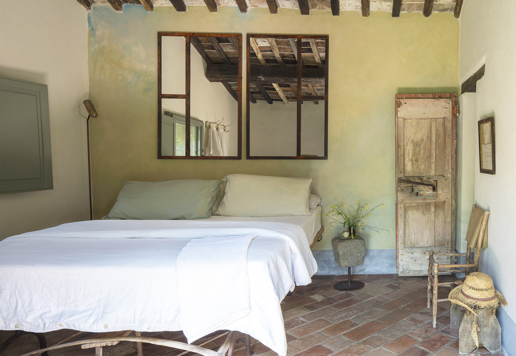 A Follonico bedroom suite with antiques, a stone floor and lots of natural light