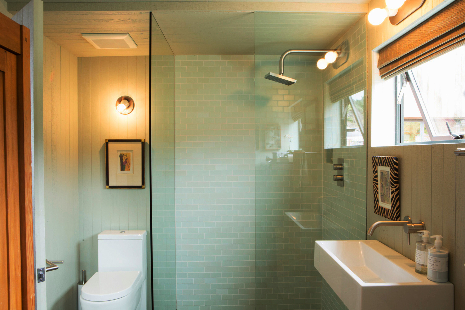 A tiled shower room with glass partitions