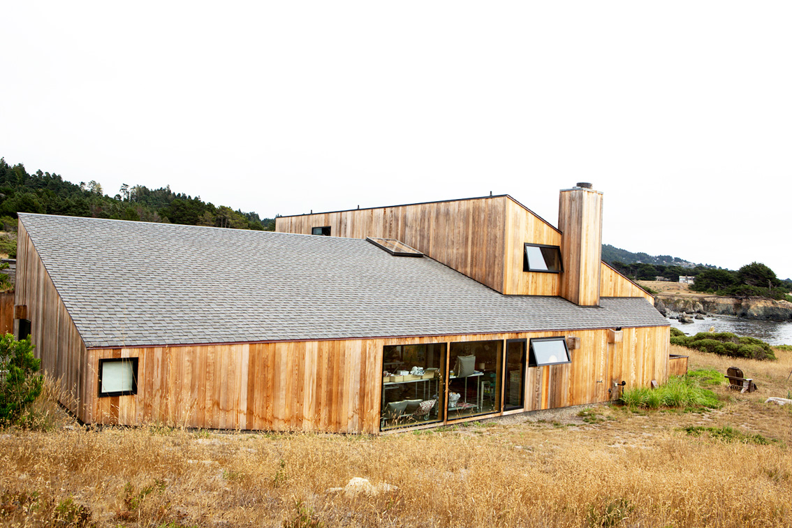 The timber clad house has a sloping roof