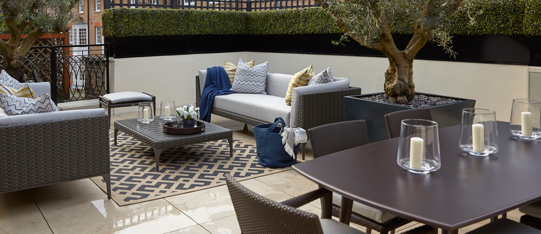 The outdoor terrace uses weather proof furniture and outdoor rugs
