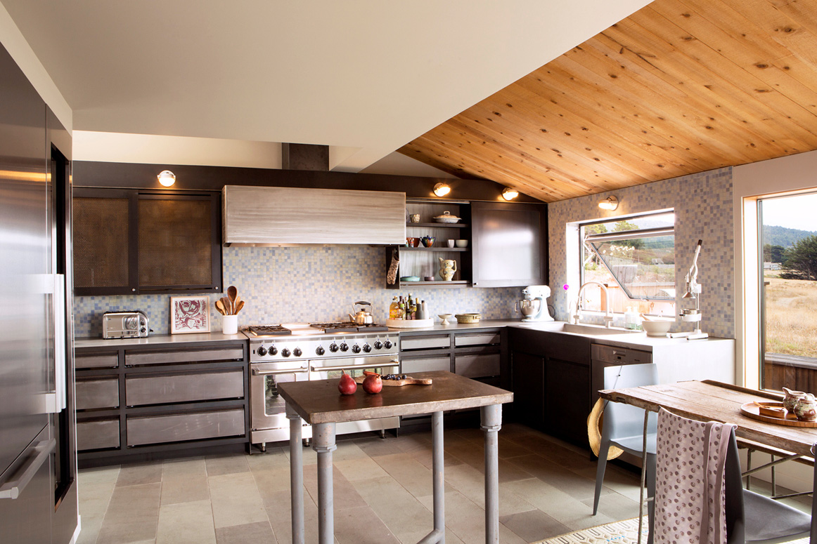 The kitchen has custom made steel units