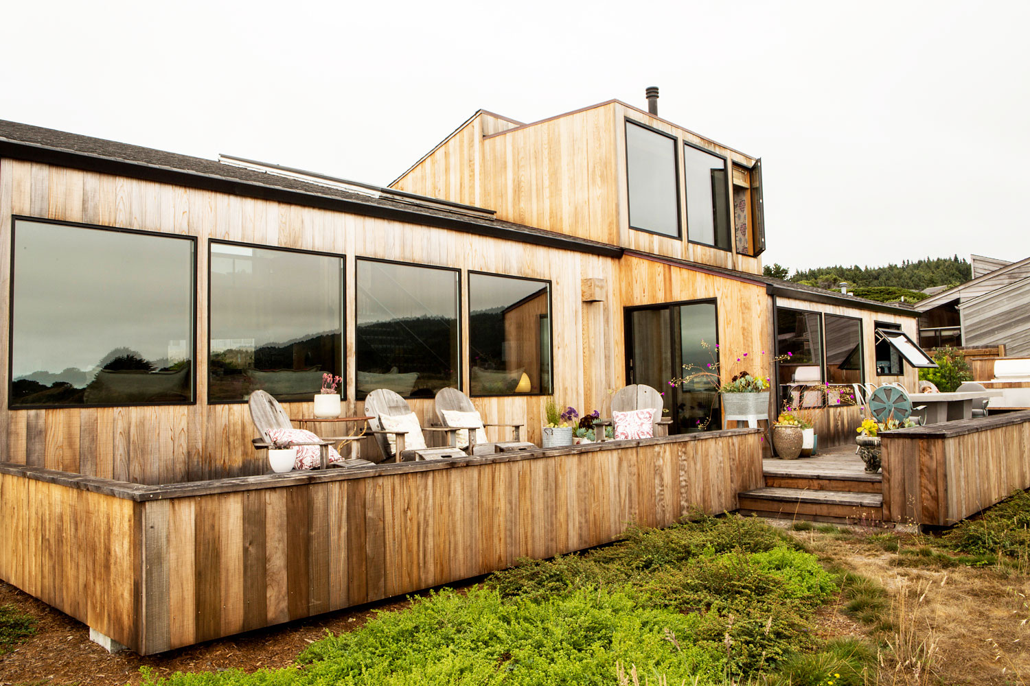 The wooden clad house has large windows