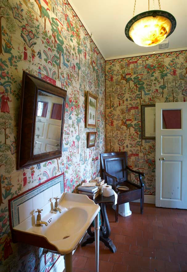 Exuberant wallpaper and an antique loo seat give this room impact