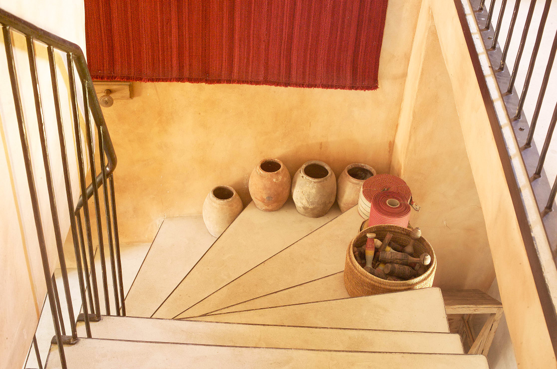 A staircase with simple iron balustrading and decorated with terracotta pots