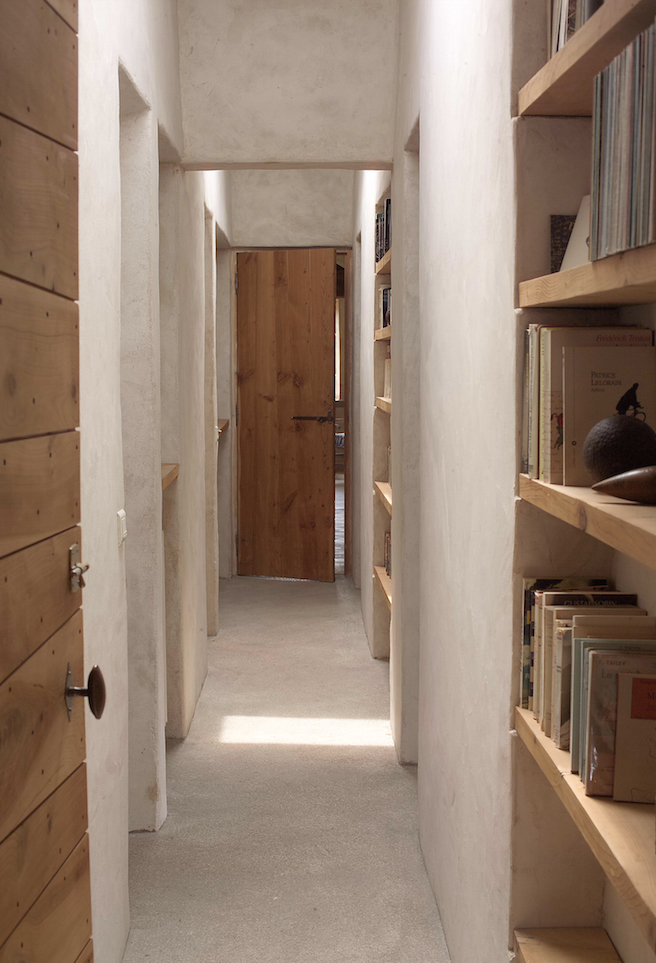 The upstairs hallway has built-in shelving and doors made from old cedar roof beams