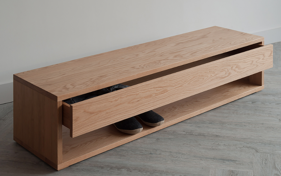 End of bed drawer unit in oak is super useful as a seat, drawer and shoe rack.