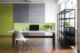 Panels on walls and a panel is cut as a desk divide to provide visual and acoustic benefit