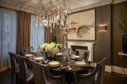 A glass chandelier hangs over the dining table