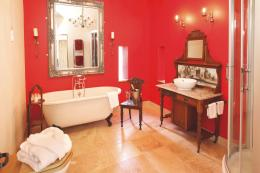 The bathroom has vibrant red walls, a popular colour in Tudor times. It has a limestone floor and roll top bath. The wooden washstand with a tiled back was found at an auction.