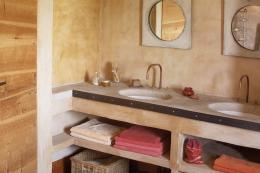 The main bathroom has two basins set into concrete
