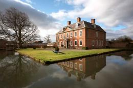 The house in Herefordshire dates back to 1700. Not so the peacock. The house has a canal-like waterway to the north and east