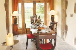 The dining room, with original stone flagstones, leads to French doors that open onto the garden. The table had once been used in a  secondary school and Niall Hardie-Hammond rescued it from a skip