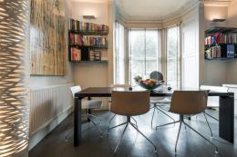 The window end of the main room is the dining area with a large dark wood veneer table