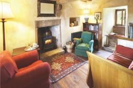 The main sitting room has wood floors and comfortable seating. The sofa was once Caroline's son's oak bateau lit cot
