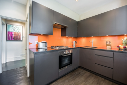 The kitchen was made by Gary Wild using birch ply and MDF.  The orange glass splash back was made by a local glazer. The floor is Amtico vinyl