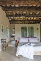 A bedroom suite with reclaimed timber, original stone floors and crisp fresh linen