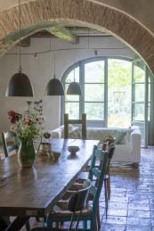 An substantial wooden dining table looks out towards French doors
