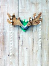 Wood offcuts are carved into an antler shapes with the end of each put in a metal plumbing unit