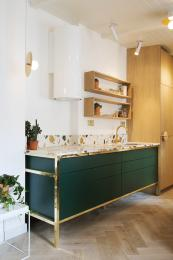 The green painted wooden sink/worktop unit in a brass frame. he worktop is an engineered marble by Max Lamb, made by Dzek