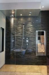 His.. modern shower room with textured wall tiles and Cumbrian slate floor