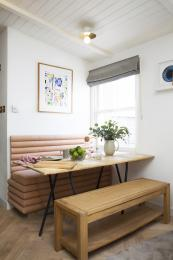 The dining table is made from recycled cheese boards. The bespoke banquette has storage under the seat