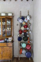 An old wooden ladder becomes a storage unit for pots and pans