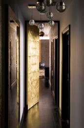 London designers Lawson Robb designed a hammered bronze door to add light and interest to this long corridor