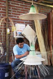 Weaver Raul Briones making a lamp using rattan and plastic bottles in Chimbarongo