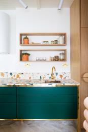 The dark green drawers contrast with the Marmoreal marble worktop