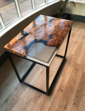 Coffee table made from reclaimed wood with plant-based resin on a metal base