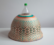 A shade hand-woven from straw by the Eperara-Siapidara people is attached to a plastic water bottle